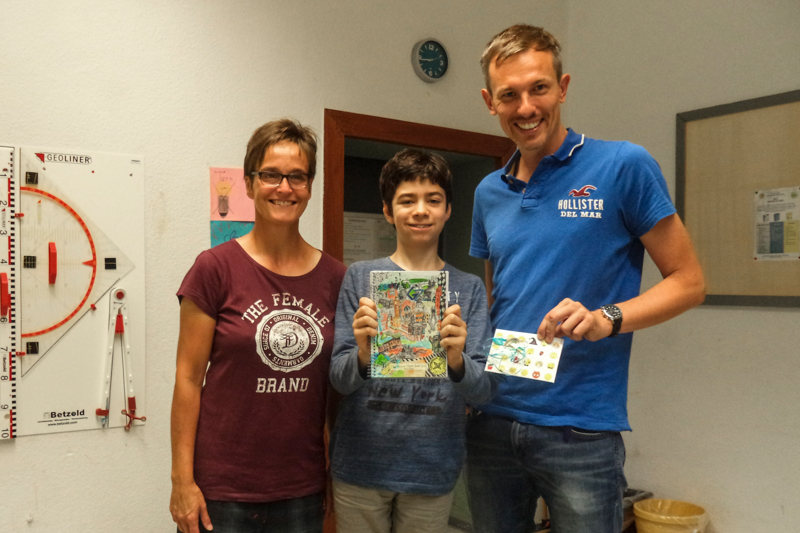 Im Beisein der Klassenlehrerin Ilona Berchem-Borell überreicht Dirk Neumann den Gutschein der Buchhandlung Fischer an Aaren Bhatti